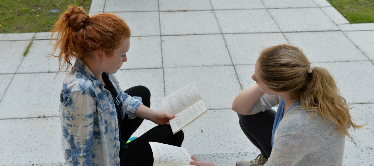 2 female students reading in Edwards Courtyard