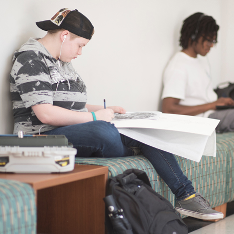 Student drawing on a bench in the hallway of Edwards College of Arts & Humanities