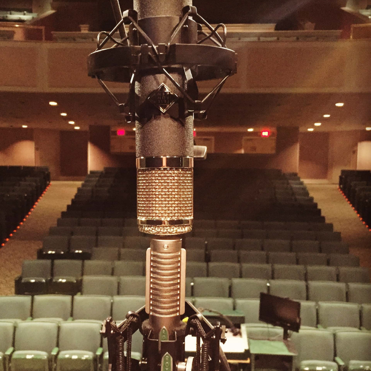 A professional-grade microphone looking out onto the audience of Wheelwright Auditorium.