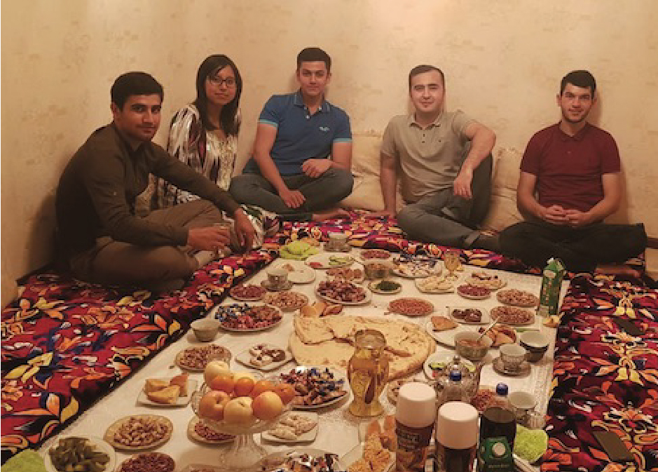 Student sitting around traditional low table in Khazahstan with other students from around the globe.