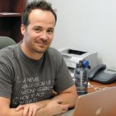 Chad Casselman at his desk with laptop - Alumni Profile