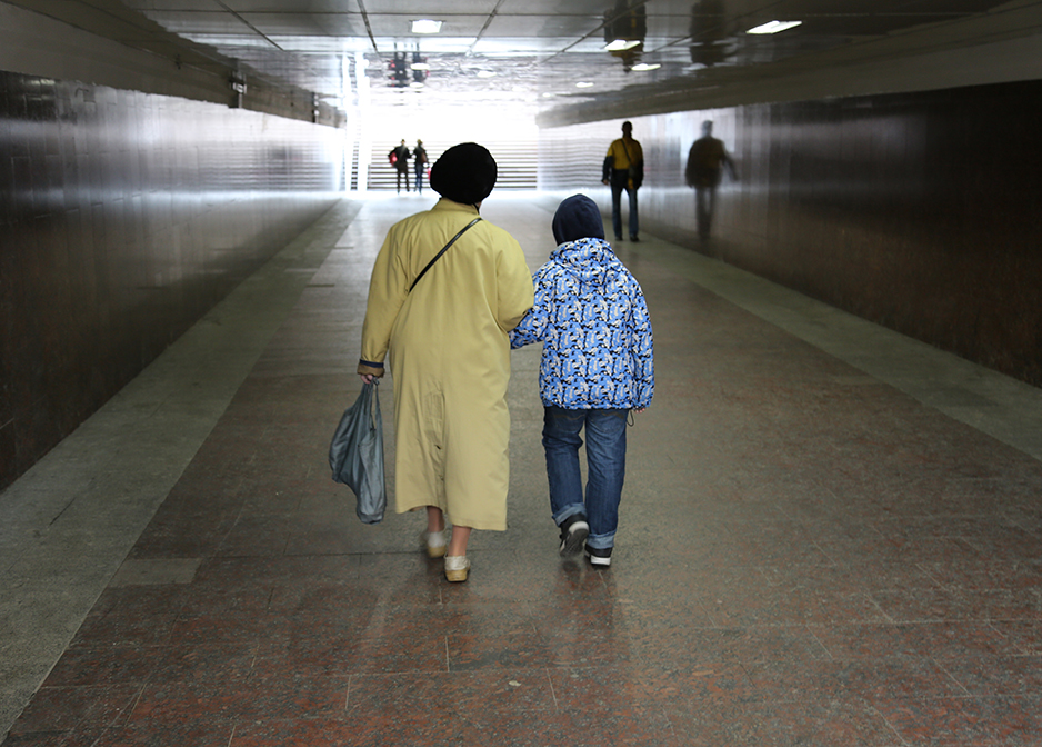 a child walks with an older lady in the entrance to the subway in Moscow