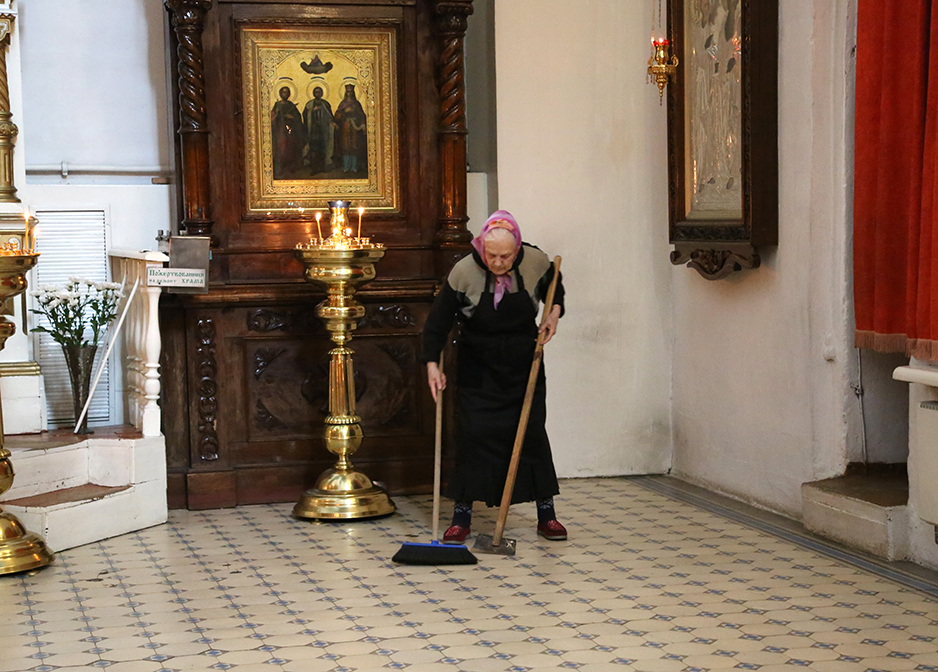 old lady sweeping church in Pskov, Russia