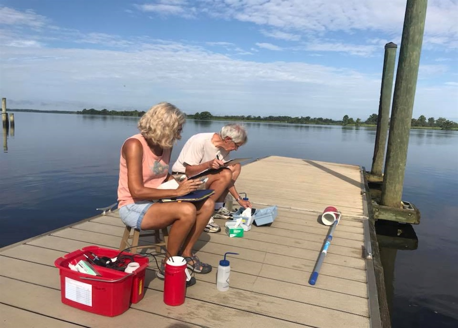 A photo of two volunteers sampling on a dock