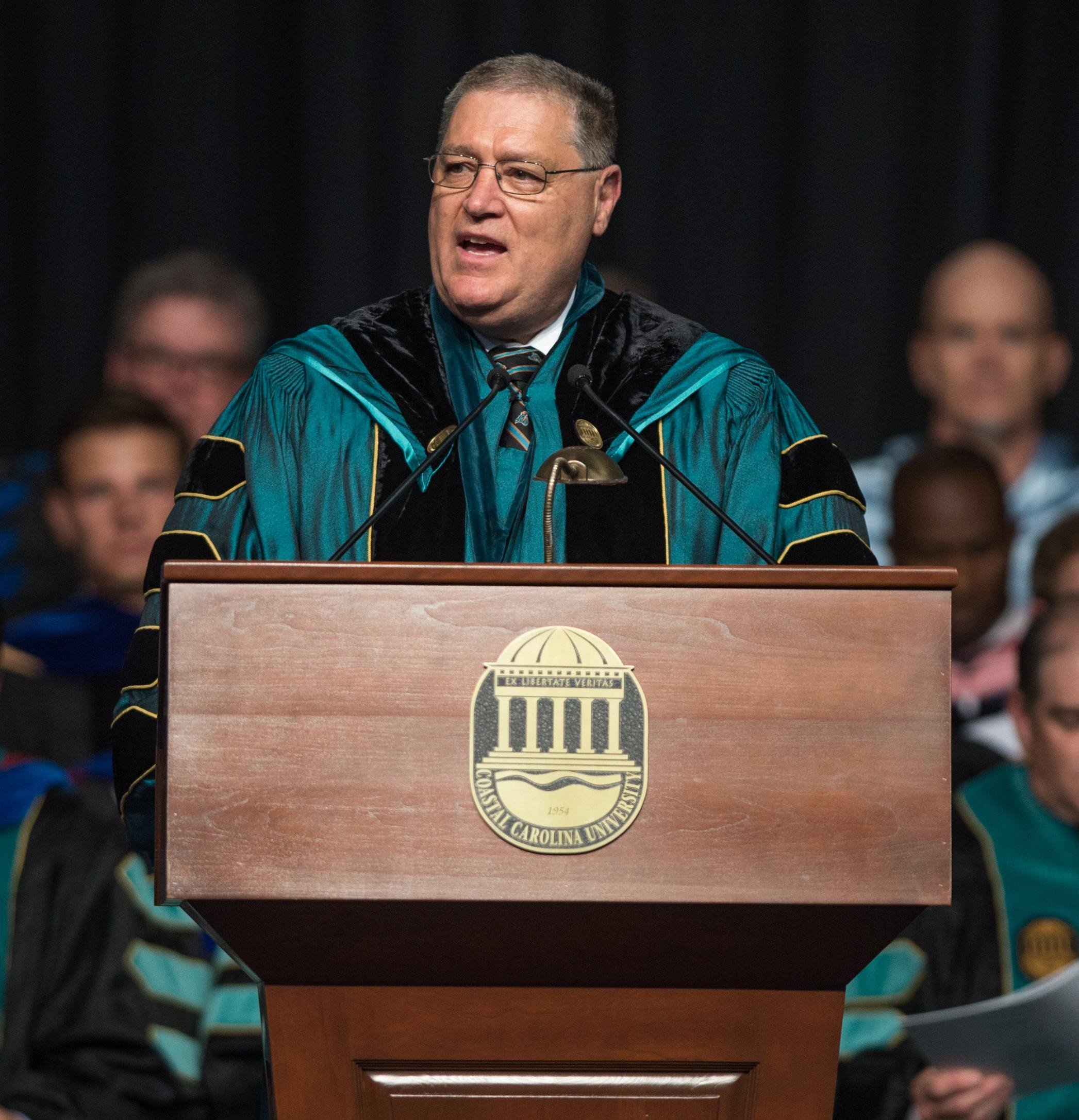 Photo of President David DeCenzo at the podium, in front of a crowd, speaking at a commencement
