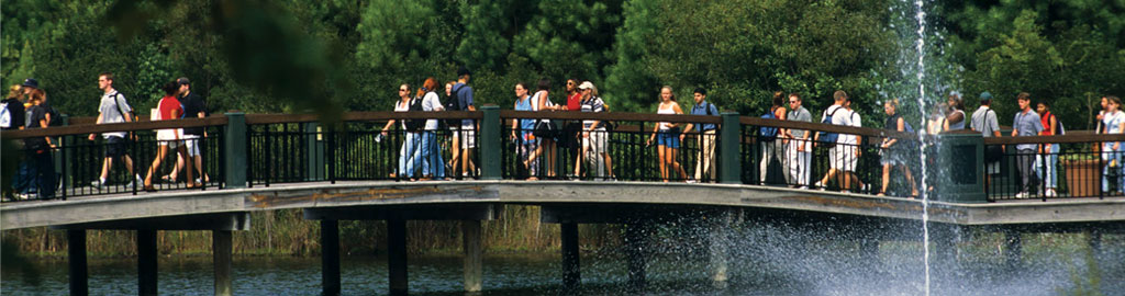 students crossing the bridge on campus